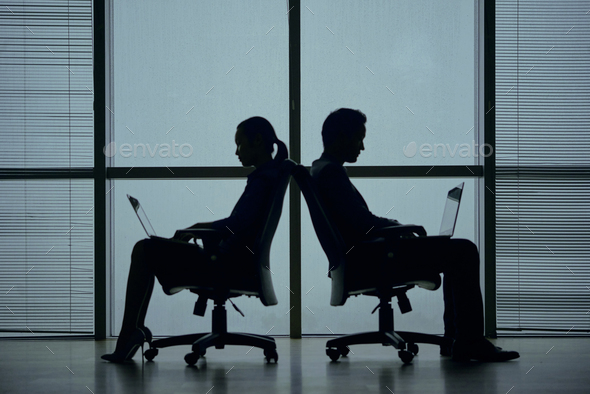 Business people sitting back to back in office chairs - Stock Photo - Images