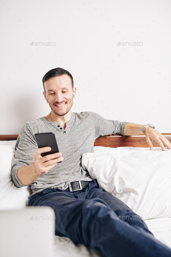Cheerful man texting friends - Stock Photo - Images