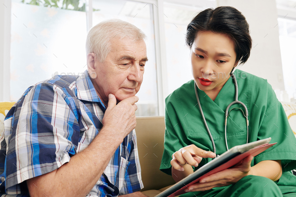 Nurse showing medical tests results to patient - Stock Photo - Images