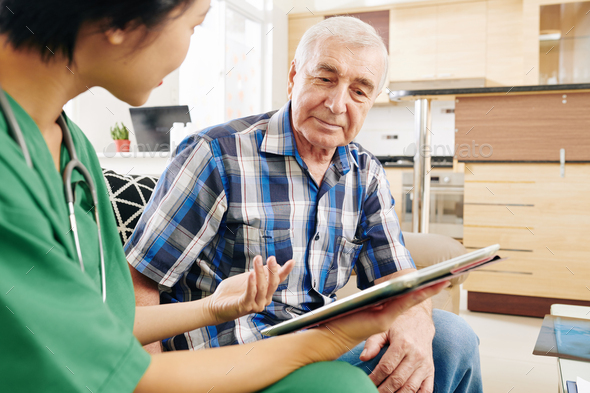 Nurse visiting old man at his apartment - Stock Photo - Images