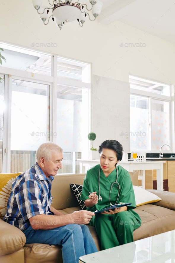 Nurse visiting elderly patient at home - Stock Photo - Images