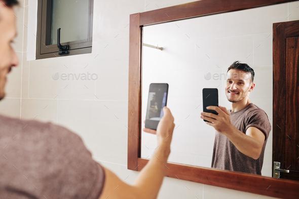 Smiling man taking selfie in bathroom - Stock Photo - Images