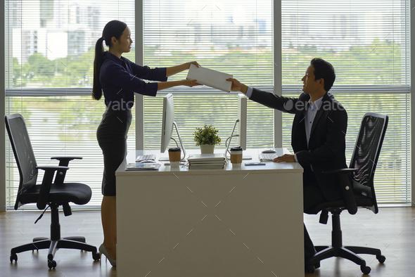 Female entrepreneur passing folder to coworker - Stock Photo - Images
