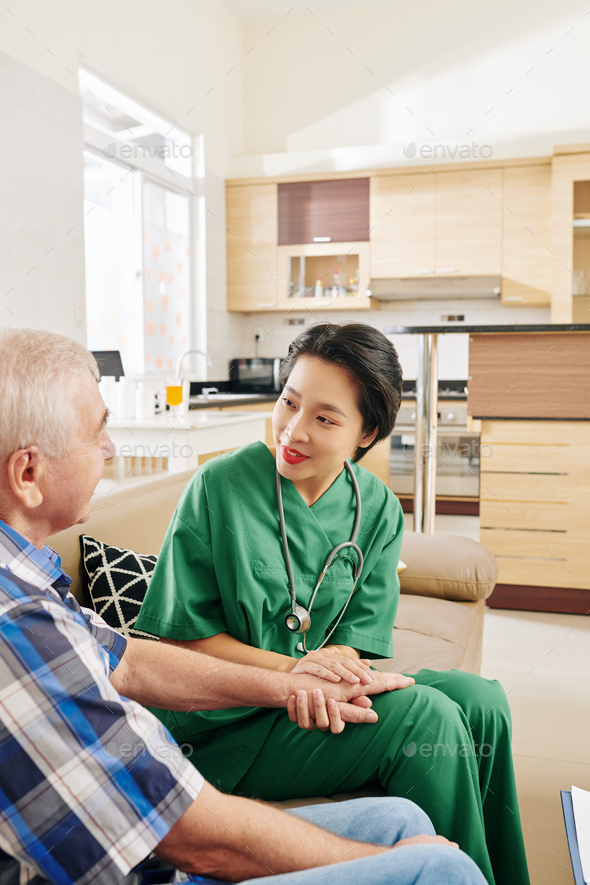 Nurse talking to senior patient at home - Stock Photo - Images