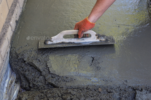 Builder smoothing the surface of screed - Stock Photo - Images