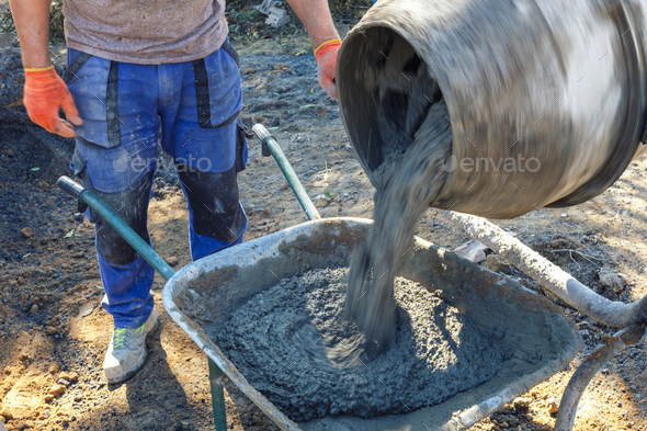 Builder pouring cement from a cement mixer - Stock Photo - Images