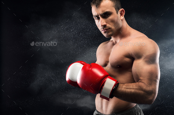 Young boxer posing on camera in red gloves - Stock Photo - Images