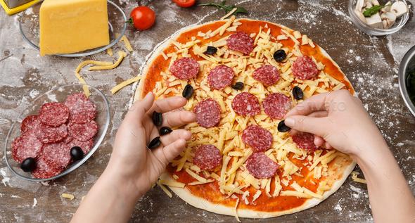 Pizzaiolo Adding Black Olives To Pizza, Preparing Pepperoni Pizza - Stock Photo - Images