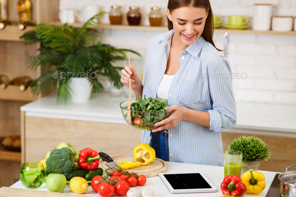 Woman Cooking Salad, Looking For Recipe Online - Stock Photo - Images