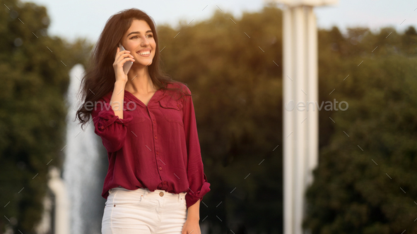 Walk outdoors. Girl talking on phone against fountain - Stock Photo - Images