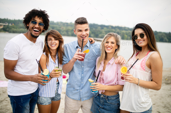 Group of friends having fun at the beach on a sunny day - Stock Photo - Images
