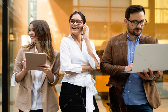 View at young business people talking and smiling outdoors - Stock Photo - Images