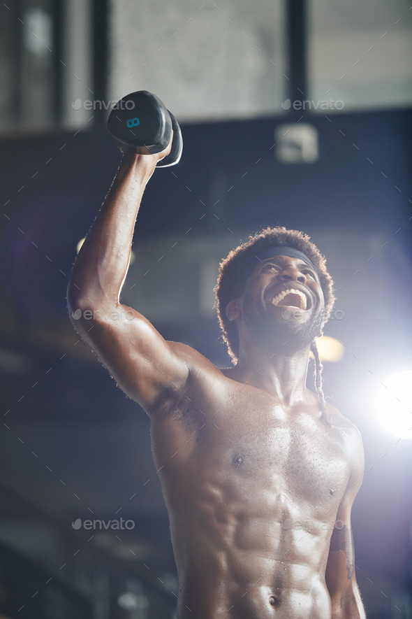 Muscular Black man lifting dumbbell - Stock Photo - Images