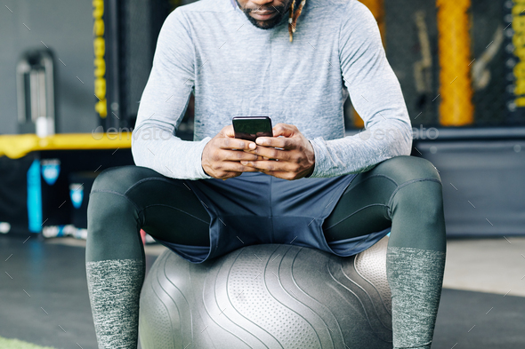 Sportsman checking health mobile app - Stock Photo - Images