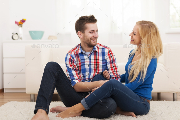 Loving couple sitting on floor in living room - Stock Photo - Images