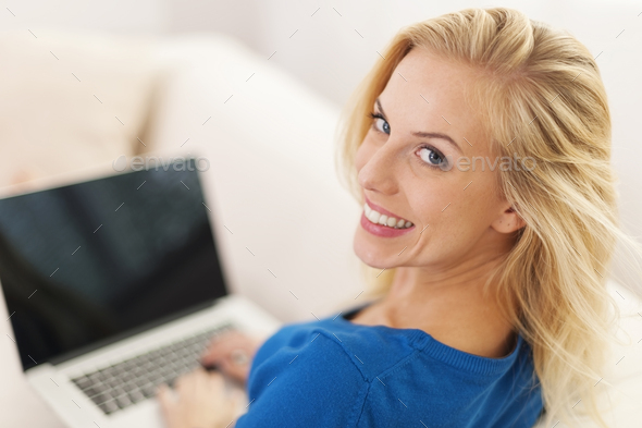 Blonde woman sitting at home with laptop - Stock Photo - Images