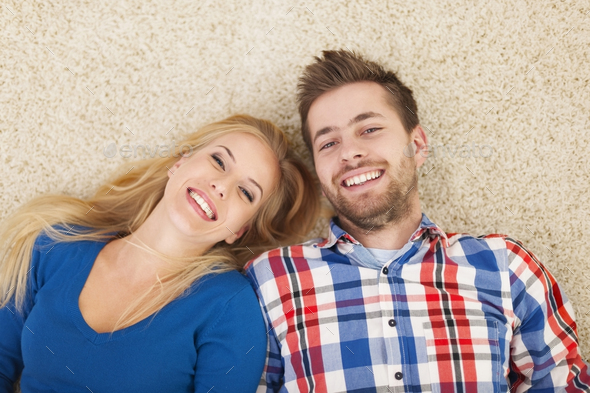 Portrait of happy couple lying down on carpet - Stock Photo - Images