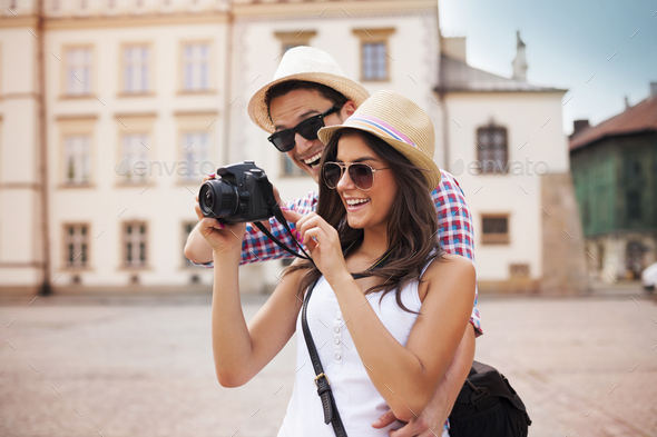 Cute couple looking on their photos on camera - Stock Photo - Images