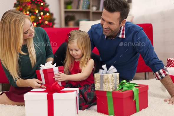 Happy family opening christmas presents - Stock Photo - Images