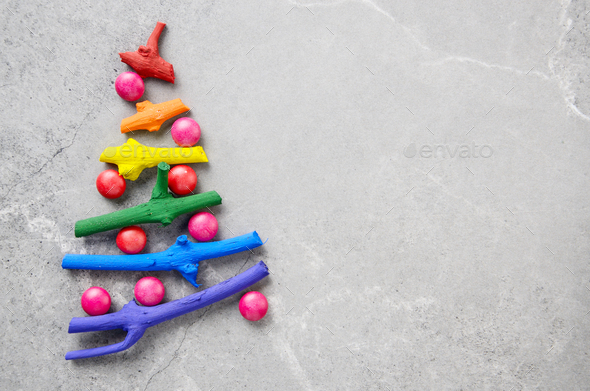 Flat lay stylized Christmas tree made of small twigs painted in - Stock Photo - Images