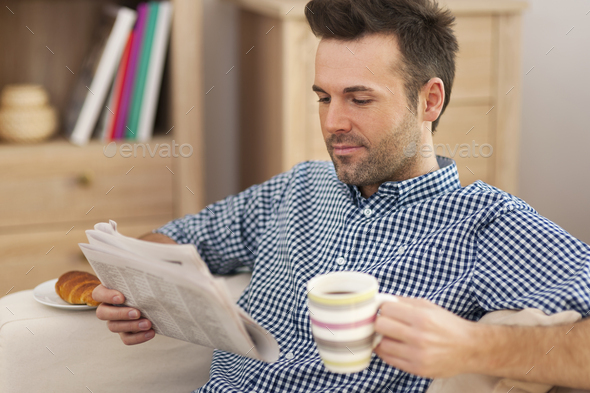 Smiling man with newspaper and cup of coffee - Stock Photo - Images