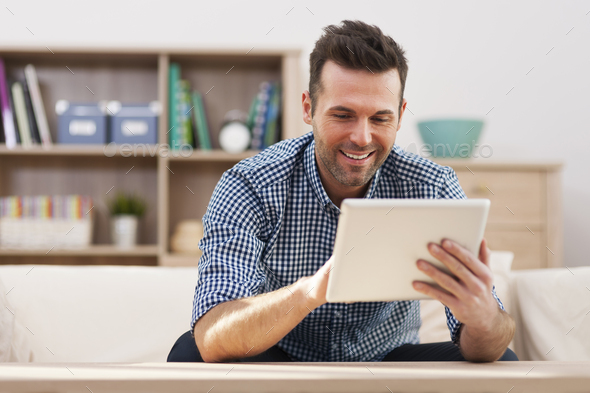Smiling handsome man using digital tablet at home - Stock Photo - Images