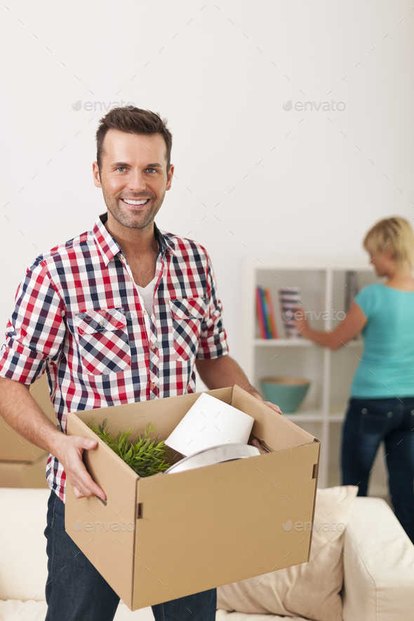 Handsome man unpacking in new home - Stock Photo - Images