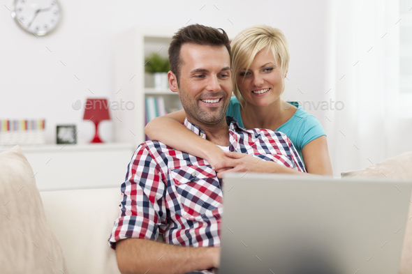 Happy couple sitting in living room and using laptop - Stock Photo - Images