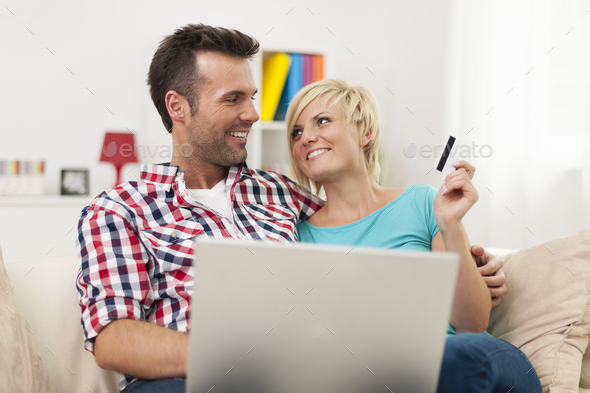 Smiling couple with laptop and credit card doing shopping - Stock Photo - Images