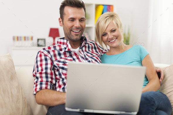 Excited couple looking on laptop at home - Stock Photo - Images