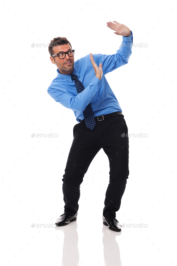 Scared businessman benting under the weight of something - Stock Photo - Images