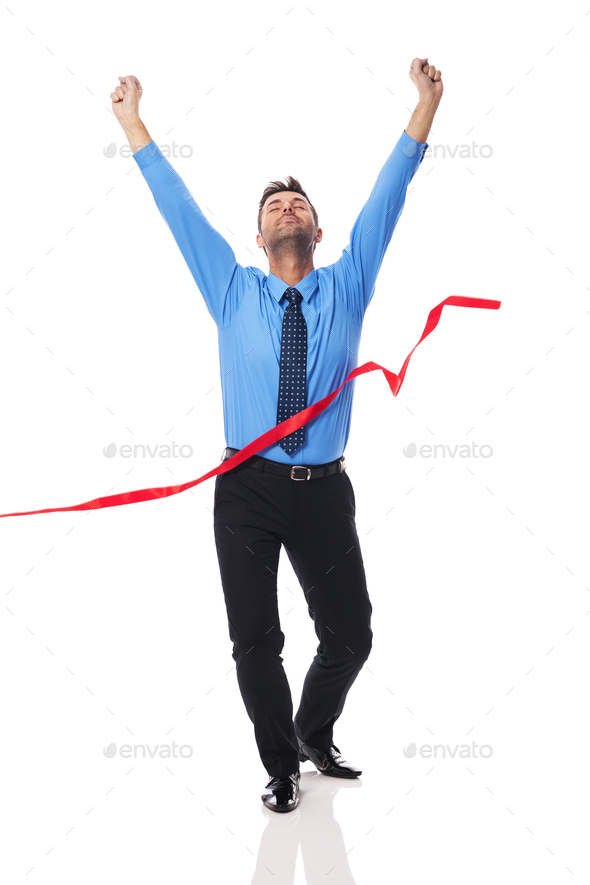 Handsome business man crossing the finish line - Stock Photo - Images