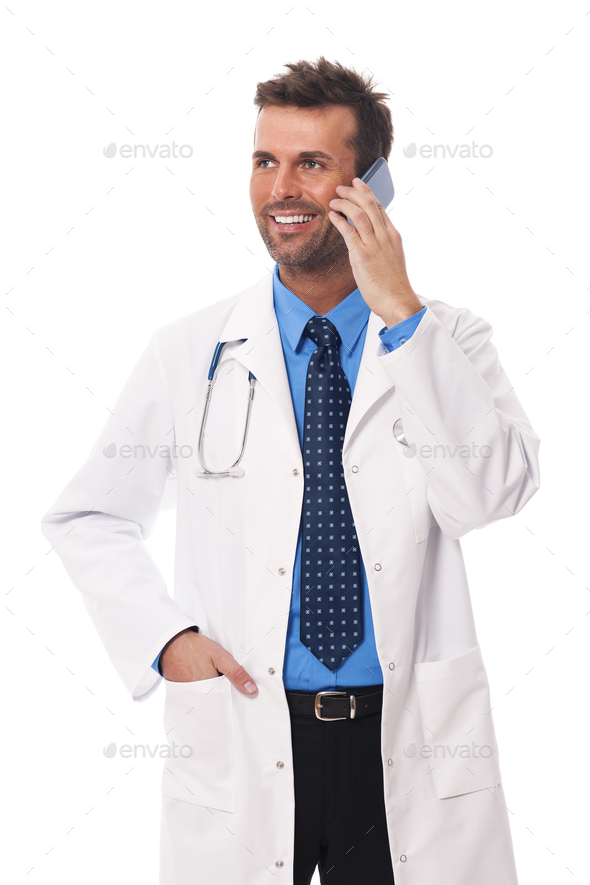 Smiling male doctor talking on mobile phone - Stock Photo - Images