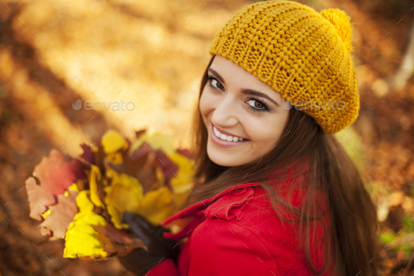 Beautiful woman holding leaves in sunny autumn day - Stock Photo - Images