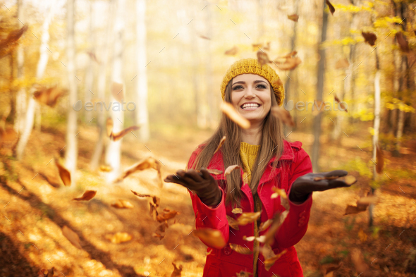 Happy woman throwing leaves - Stock Photo - Images