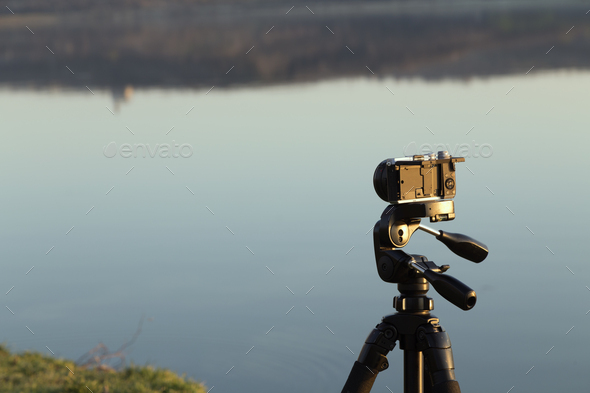 Camera on a tripod on the background of the lake. - Stock Photo - Images