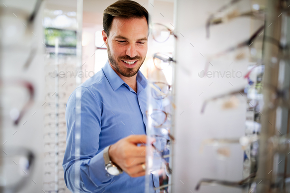 Handsome man choosing glasses in optics store - Stock Photo - Images