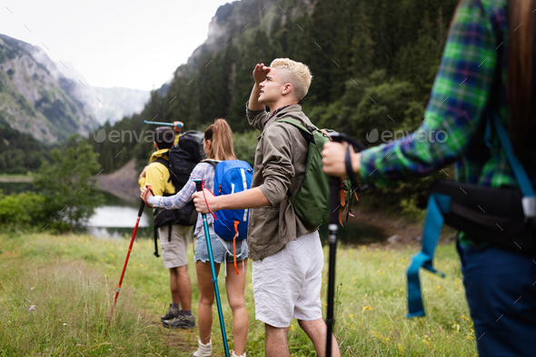 Group of young friends hiking in countryside. Multiracial happy people travelling in nature - Stock Photo - Images