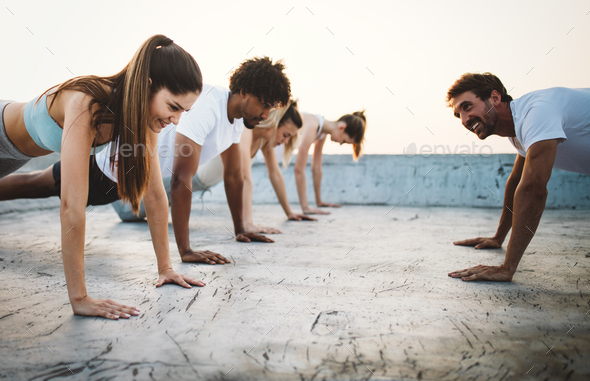 Group of happy fit friends exercising outdoor in city - Stock Photo - Images