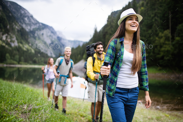 Group of friends hikers walking on a mountain at sunset - Stock Photo - Images