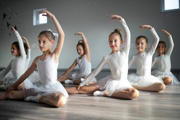 Group of little ballerinas girls doing exercises in dance school - Stock Photo - Images