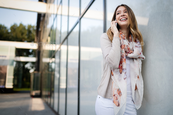 Outdoors portrait of beautiful young girl laughing and using cell phone - Stock Photo - Images