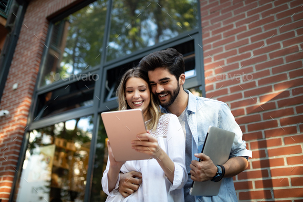 Young couple using a digital tablet together and smiling - Stock Photo - Images