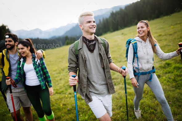 Group of friends are hiking in mountain. Young people walking through countryside - Stock Photo - Images