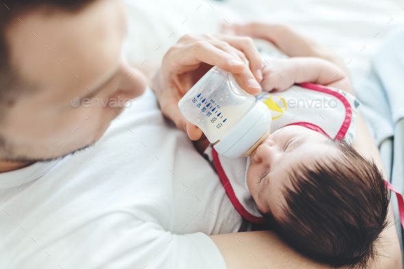 Young white father feeding baby with bottle - Stock Photo - Images