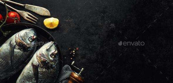 Dorado fish with ingredients on dark - Stock Photo - Images