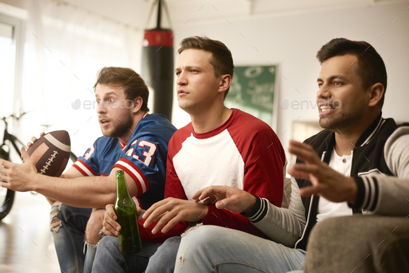 Unhappy men while watching american football - Stock Photo - Images