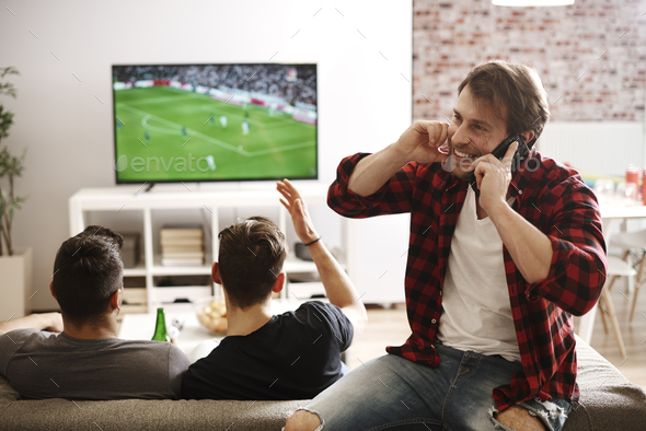 Man talking by phone while soccer match - Stock Photo - Images