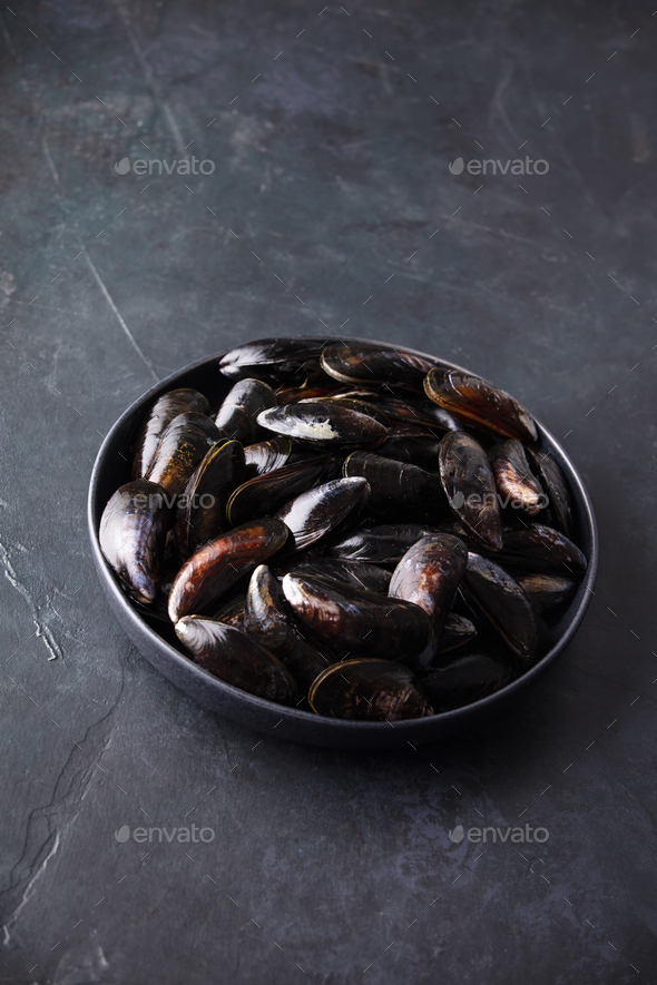 Bowl with fresh raw mussels ready to cook on dark background - Stock Photo - Images