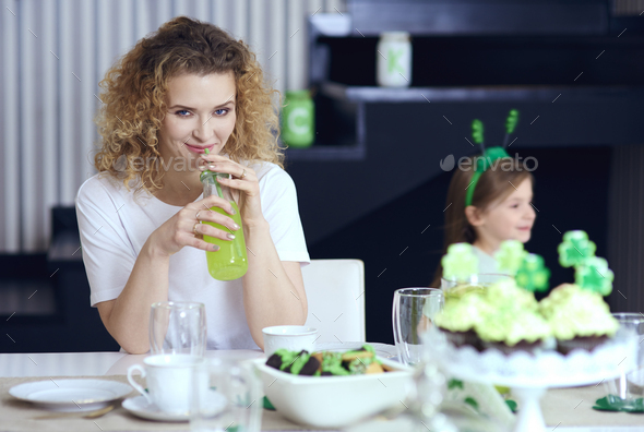 Woman drinking cocktail at Saint Patrick's Day party - Stock Photo - Images